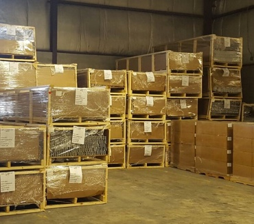 A warehouse with palletized and wrapped garage door parts.